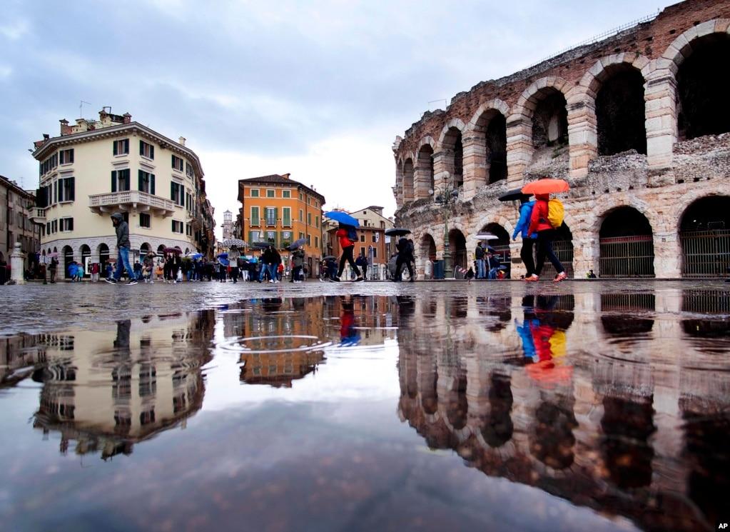 Туристы гуляют под проливным дождем вдоль старой арены, справа, и зданий Старого города в Вероне, Италия.