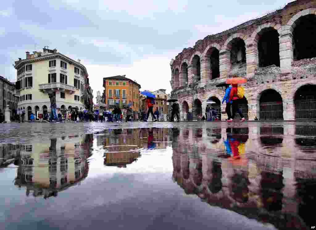 Tourists walk in the pouring rain along the old arena, right, and buildings of the old town in Verona, Italy.
