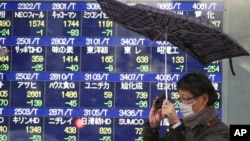 A man reacts to a gust of wind as it starts to snow, in front of an electronic stock board at a securities firm in Tokyo, Feb. 4, 2014.
