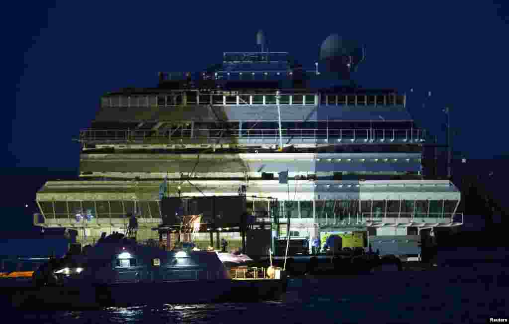 The damaged side of the capsized cruise liner Costa Concordia is visible after the ship was righted outside Giglio harbor, Italy, Sept. 17, 2013.