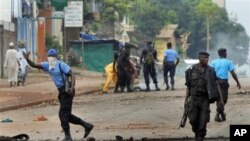 Guinean police carrying automatic weapons clear the mostly Peul suburb of Bambeto in Conakry, Guinea, Tuesday, Nov. 16, 2010, as groups of UFDG youth set up barricades.