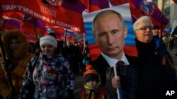 Pro-government activists with Russian flags carry a portrait of President Vladimir Putin as they march through downtown Moscow to mark People's Unity Day, Nov. 4, 2014.