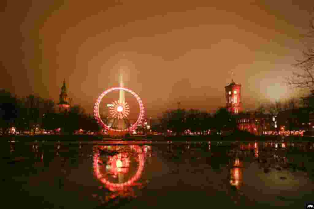 The ferris wheel at the Christmas market on the Alexanderplatz is reflected in a puddle at rainy and foggy weather in Berlin on Monday, Nov. 22, 2010. The Christmas markets in Berlin open on Monday for the Christmas season. (AP Photo/Markus Schreiber)