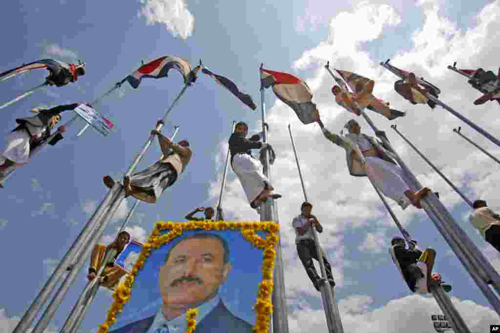 Supporters of Yemen's President Ali Abduallah Saleh stand on flag poles celebrating his return to Sanaa, Yemen, Friday, Sept. 23, 2011. President Ali Abdullah Saleh made a surprise return to Yemen on Friday after more than three months of medical treatmen