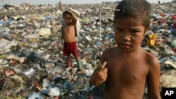 Child scavengers pose with their metal hooks used to rummage garbage amidst a mountain of trash in a Manila dumpsite, August 20, 2002.