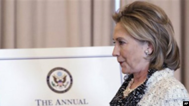 Secretary of State Hillary Rodham Clinton walks past a portrait of the late Ambassador Richard Holbrooke, Friday, Jan. 14, 2011, at the State Department in Washington.