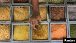 FILE - An employee collects lentils from a container inside a grocery store at a residential area in Mumbai, India.