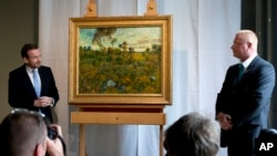 "Photographers take pictures as Van Gogh Museum director Axel Ruger, left, and a security guard, right, stand next to newly discovered ""Sunset at Montmajour"" after unveiling the painting by Dutch painter Vincent van Gogh during a press conference at the mu"