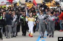 First torch bearer, South Korean figure skater You Young, center, runs as she holds an Olympic torch during the Olympic Torch Relay at Incheon Bridge in Incheon, South Korea, Wednesday, Nov. 1, 2017.