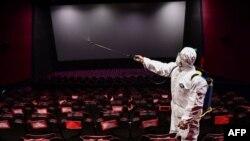 遼寧省瀋陽市一家電影院的工人在給影院噴灑消毒液準備重新開業。 (2020年3月25日)