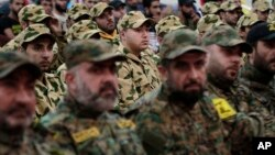FILE - Hezbollah fighters listen to Hezbollah leader Sheik Hassan Nasrallah, as he speaks via video link during a rally to mark the Hezbollah martyr day, in the southern suburb of Beirut, Lebanon, Beirut, Lebanon, Wednesday, Nov. 11, 2015.