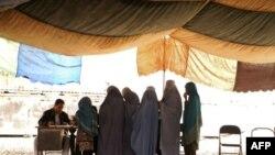 صف زنان افغان برای گرفتن لباس های گرم، ذغال، و تدارکات دیگر
