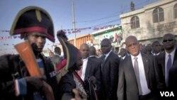 Agoch, yon ayisyen ki degize ak kostim jeneral Jean-Jacques Dessalines, anperè Ayiti, pale ak Prezidan Michel Martelly, a dwat, pandan yon seremoni nan Port-au-Prince, Haiti (17 Oct. 2011)