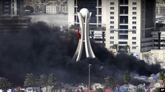 Black smoke billows from burning tents in Pearl Roundabout in the Bahraini capital, Manama, on March 16, 2011, when anti-government protesters were dislodged from the square by security forces