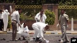 Petugas forensik mengumpulkan barang bukti di lokasi ledakan bom bunuh diri di ibukota Sana'a, yang menewaskan 96 tentara Yaman, Senin (21/5).
