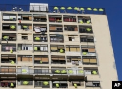 Yellow vests hang on the rooftop and at windows of an apartment building, Dec. 7, 2018, in Marseille, southern France.