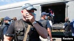 MH17 မေလးရွားပ်က္က်ေလယာဥ္ေပၚ လုိက္ပါသြားသူေတြရဲ႕ ႂကြင္းက်န္တဲ့ ႐ုပ္ကလာပ္ေတြကို သယ္ေဆာင္ဖို႔ ေဆာင္ရြက္ေနတဲ့ ဒတ္ခ်္ ႏိုင္ငံသားေတြနဲ႔အတူ ေတြ႔ရစဥ္။ (ဇူလိုင္ ၂၁၊ ၂၀၁၄)
