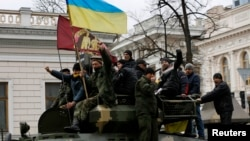 Anti-Yanukovich protesters wave a Ukranian flag atop a Ukranian Army Armoured Personnel Carrier (APC) outside the parliament building in Kiev February 27, 2014. Activists gathered outside parliament in Kiev as deputies vote for a new national unity govern