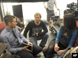 "Director Duncan Jones, center, with Jake Gyllenhaal and Michelle Monaghan on the set of ""Source Code"""
