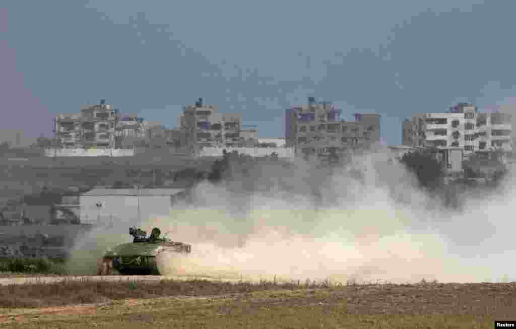 An Israeli armored personnel carrier (APC) drives back into Israel after crossing the northern Gaza Strip border (seen in background), July 28, 2014.