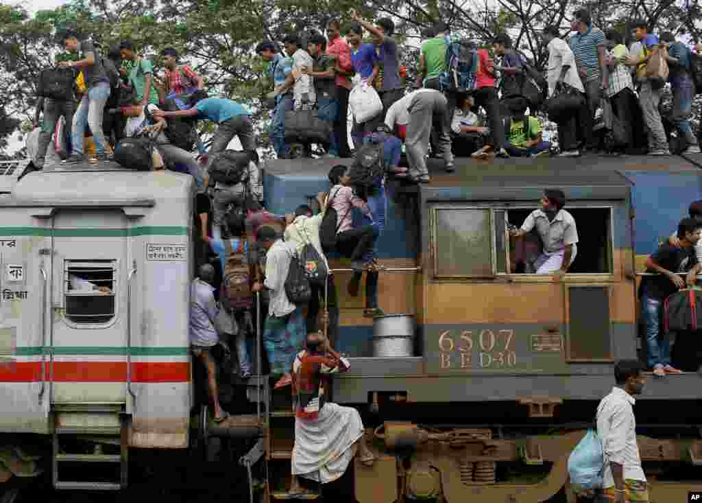 Bangladeshi Muslims try to climb on to the roof of an overcrowded train as they head to their homes ahead of Eid al-Fitr at a railway station in Dhaka.
