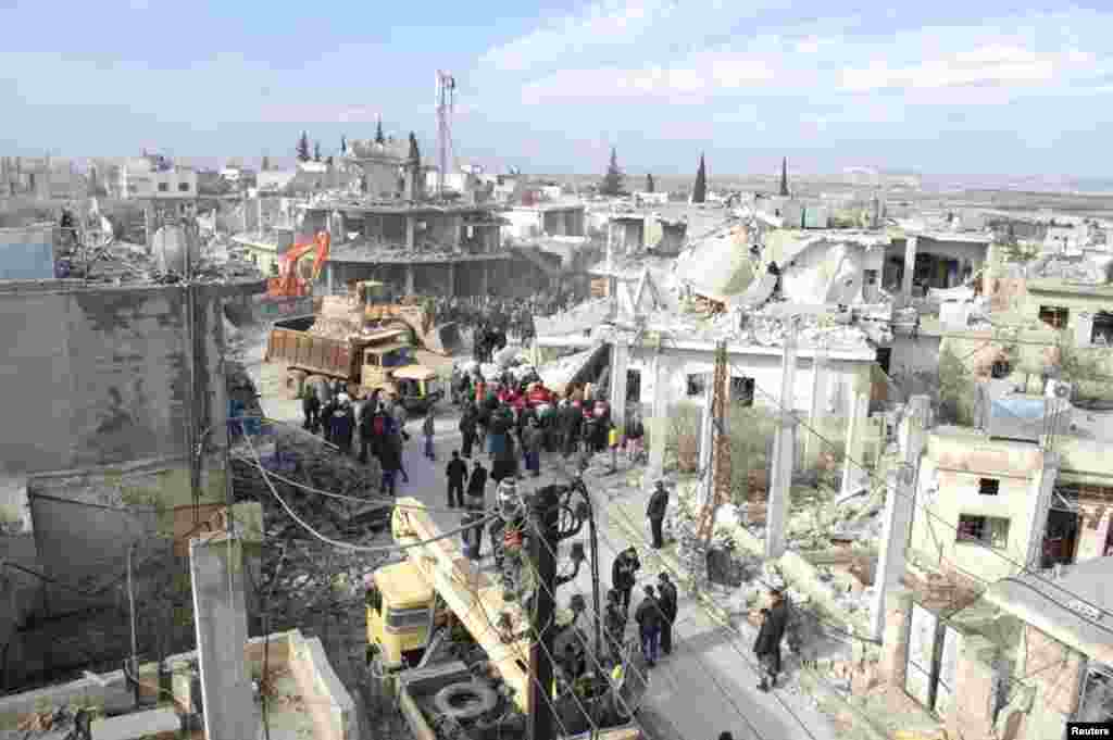 Bystanders look on as crews begin clearing the wreckage of a car bomb that exploded near a school in Al-Kafat, Syria, Jan. 9, 2014.