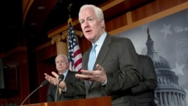 Sen. John Cornyn, R-Texas, right, accompanied by Sen. John McCain, R-Ariz., gestures during a news conference on Capitol Hill in Washington, Tuesday, June 26, 2012