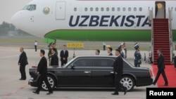 FILE - Chinese guards walk alongside the car of Uzbekistan President Shavkat Mirziyoyev in Qingdao city, Shandong province, China, June 8, 2018.