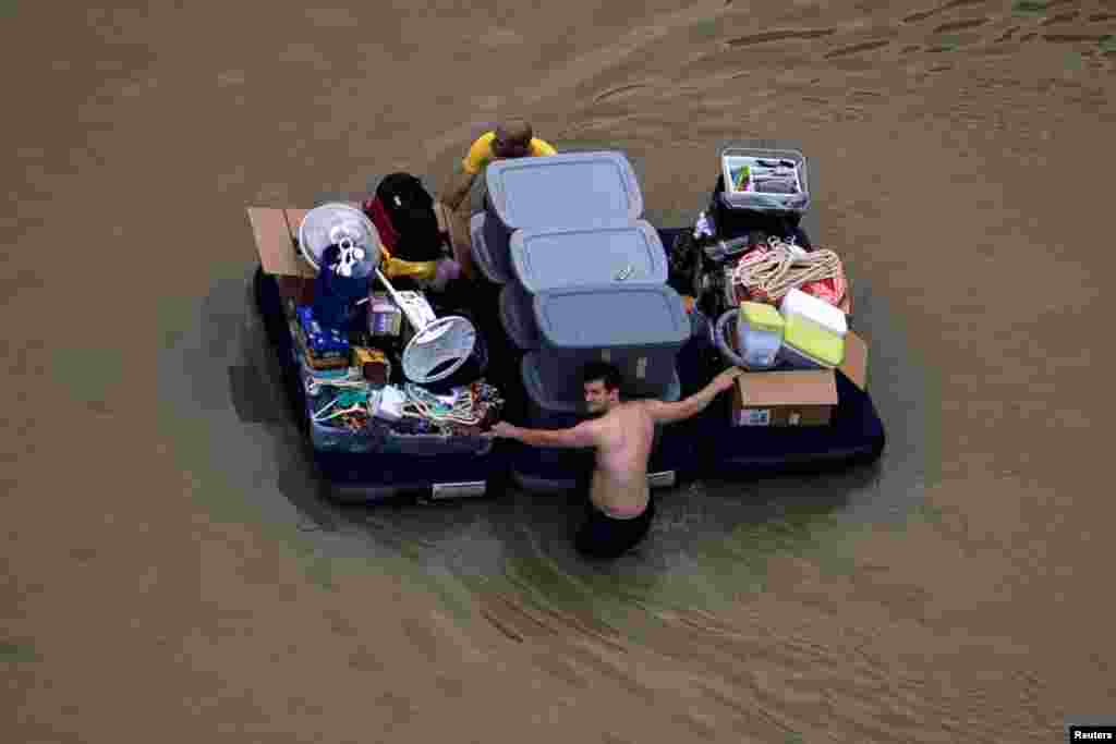 Residents wade with their belongings through flood waters brought by Tropical Storm Harvey, in Houston, Texas, Aug. 30, 2017.