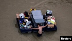 Residents wade with their belongings through flood waters brought by Tropical Storm Harvey in Northwest Houston, Texas, U.S. August 30, 2017.