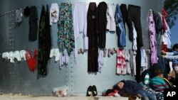 A kid sleeps under laundry at the migrant and refugee registration camp in Moria village on the northeastern Greek island of Lesbos, Nov. 12, 2015.
