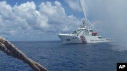 지난해 9월 남중국해 스카보로 암초 주변에서 조업 중인 필리핀 어선을 향해 중국 경비정이 접근하고 있다. (자료사진)
