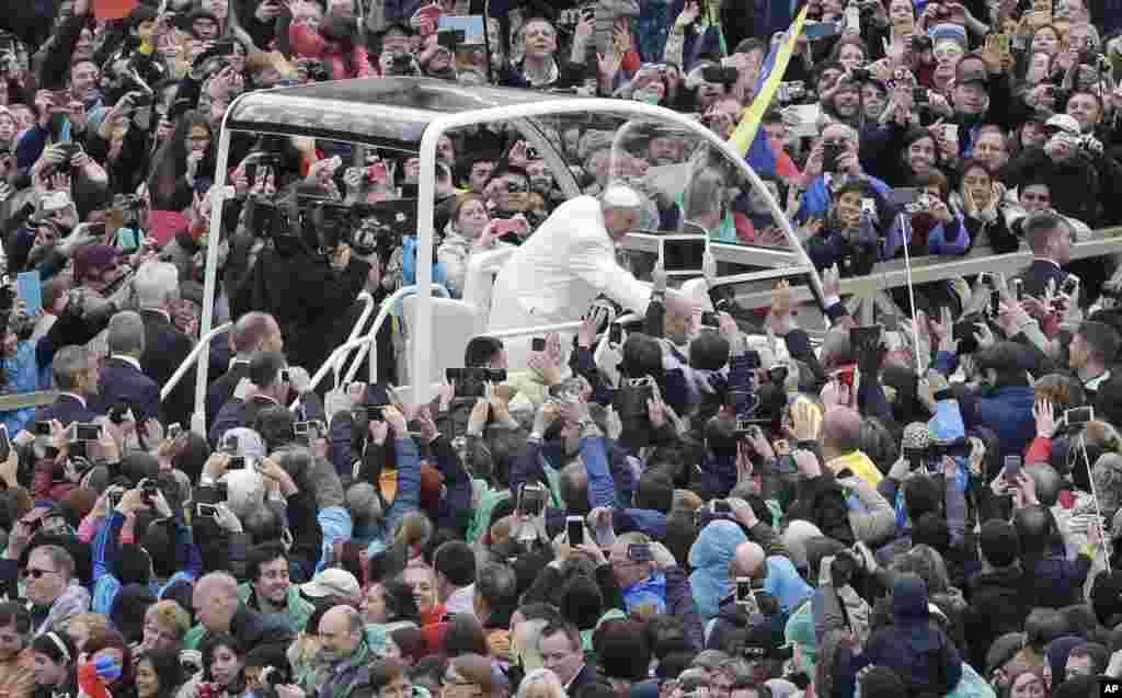 Paus Fransiskus menyapa umatnya di lapangan Santo Petrus di Vatikan, 5 April 2015.