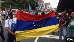 Manifestantes con la bandera de Venezuela piden cambios radicales en el gobierno de su país. 1 de abril de 2017. Foto: Álvaro Algarra / VOA.