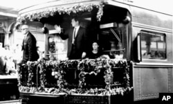 FILE - Sen. Edward M. Kennedy waves from the rear platform of the observation car bearing the remains of his slain brother, Sen. Robert F. Kennedy, as the funeral train passed through North Philadelphia Station, June 8, 1968.