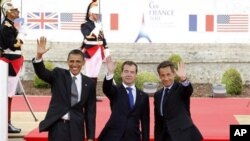 From left, US President Barack Obama, Russian President Dmitry Medvedev and French President Nicolas Sarkozy wave as they arrive for a lunch meeting at the Villa le Cercle during the G8 summit in Deauville, France, Thursday, May 26, 2011. G8 leaders, in a