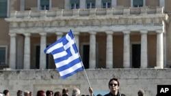 一名希臘婦女星期天在雅典國會大樓前舉著希臘國旗抗議政府大規模削減開支和降低工資