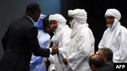 Le ministre malien des affaires étrangères Abdoulaye Diop (G) salue des représentants des groupes armés au terme d'une cérémonie de paix à Alger, le 1er mars 2015.
