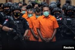 Petugas Kepolisian Indonesia mengawal tersangka penyelundup narkoba saat konferensi pers di Mabes Polri, setelah petugas berhasil mengamankan 2,5 ton sabu dari jaringan Timur Tengah, Malaysia, dan Indonesia, di Mabes Polri, 28 April 2021. (Antara Foto/M Risyal Hidayat/via REUTERS)