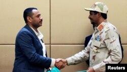 Poignée de main entre le chef adjoint du Conseil militaire de transition, Mohamed Hamdan Dagalo, et le leader de la coalition de l'opposition, Ahmad al-Rabiah, lors d'une cérémonie de signature à Khartoum, au Soudan, le 4 août 2019.