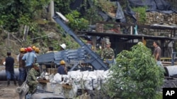 Rescue workers stand in front of the coal mine La Preciosa after an explosion at the mine in Sardinata, Norte de Santander province, January 27, 2011