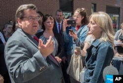 "A resident (right) confronts Montreal's Mayor Denis Coderre and Lucie Charlebois (center) Minister for Rehabilitation, Youth Protection, Public Health and Healthy Living, June 26, 2017, during the inauguration of a ""safe injection site."""