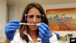 Tiến sĩ Felicity Hartnell, nghiên cứu sinh lâm sàng của trường đại học Oxford, cầm trong tay ống nghiệm vaccine chống Ebola thử nghiệm, 17/9/2014.