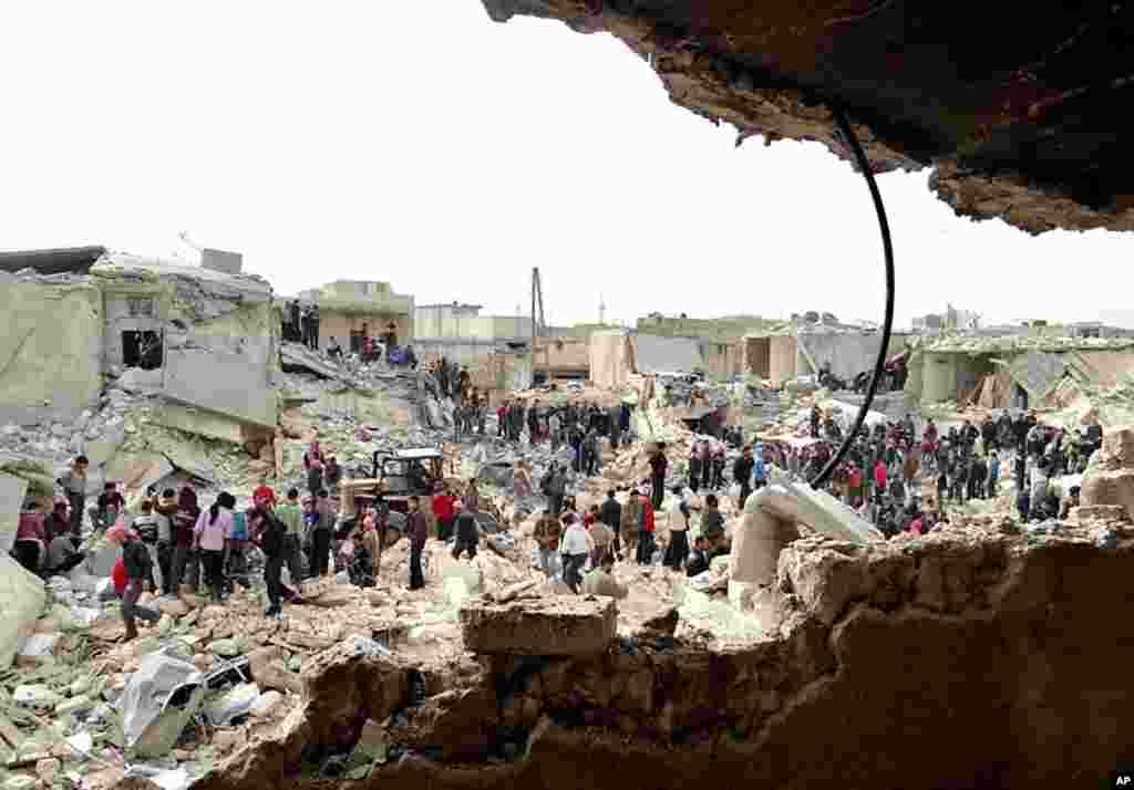 A citizen journalism image provided by the Aleppo Media Center AMC shows people searching the rubble after houses were hit by a missile fired by Syrian government forces in Ard Al-Hamra, Aleppo, Syria, Feb. 26, 2013.