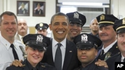 U.S. President Barack Obama poses with officers of the First Precinct police station in lower Manhattan during a visit to the World Trade Center site in New York, May 5, 2011.