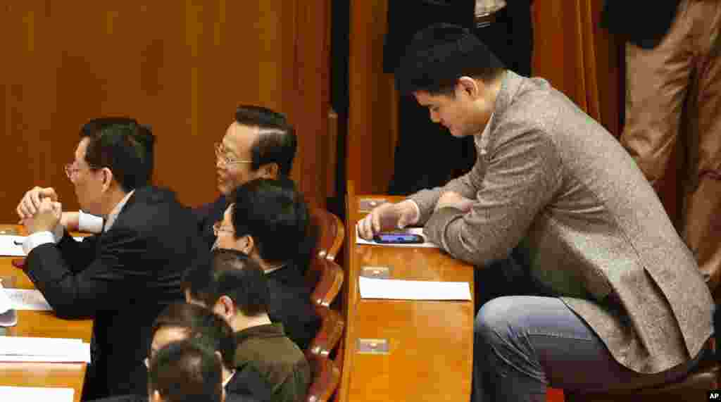 Yao Ming, former NBA basketball star and a delegate to the Chinese People's Political Consultative Conference, looks at his phone during the closing ceremony of the CPPCC in Beijing's Great Hall of the People, China.