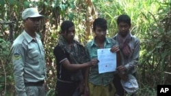 A ranger of Cambodia's 3,000 square kilometer Phnom Samkos Wildlife Sanctuary stands next to three Cambodian youth who were found entering the park illegally and made to agree not to enter again in the future, before they were released. The sanctuary lies