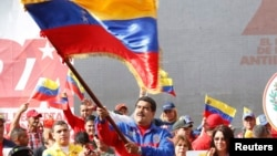 "This Venezuelan government photo shows President Nicolas Maduro waving a flag to celebrate the anniversary the ""Caracazo"" revolutionary uprising; in a speech at the rally, he announced the arrest of a U.S. pilot for alleged spying, Feb. 28, 2015."