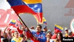 Tổng thống Venezuela Nicolas Maduro phất cờ trong cuộc tuần hành kỷ niệm cuộc cách mạng 'Caracazo'. Trong bài phát biểu tại cuộc mít-tinh, ông Maduro cho biết chính quyền của ông vừa bắt giữ một phi công Mỹ bị cáo buộc làm gián điệp.