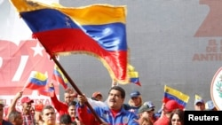 "This Venezuelan government photo shows President Nicolas Maduro waving a flag to celebrate the anniversary of the ""Caracazo"" revolutionary uprising; in a speech at the rally, he announced the arrest of a U.S. pilot for alleged spying, Feb. 28, 2015."